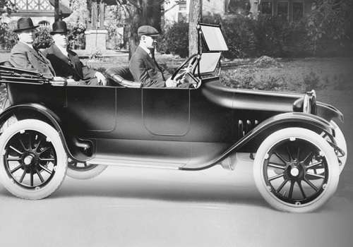 Horace and John Dodge being driven in one of their early cars