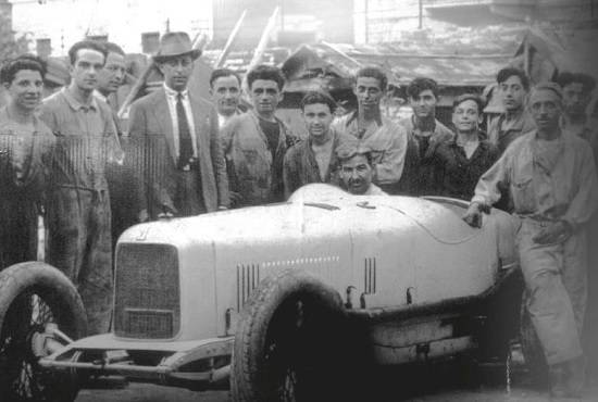 The Maserati brothers with employees and one of their sport cars in 1930